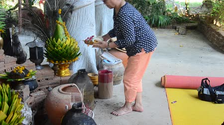 Asian thai old woman pray flower and burning incense at joss stick pot or thurible for respect with buddha statue and god at temple Thailand.