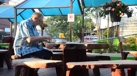 German old man sit on wooden chair and eating breakfast set and drinks hot coffee in morning time at outdoor of resort in Lampang, Thailand 影像素材