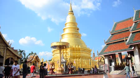 Asian thai people and foreigner people respect praying and walk visit gold chedi at Wat Phra That Hariphunchai temple in Lamphun, Thailand.
