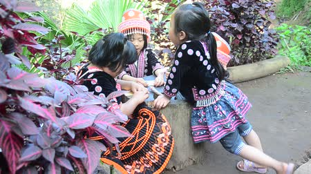 Children Ethnic Hmong wear costume traditional and playing with friends at Doi Pui Tribal Village and National Park in Chiang Mai, Thailand.