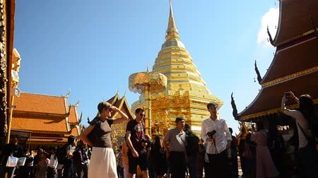 заслуга : Asian thai people and foreigner respect pray and posing take photo with gold chedi at Wat Phra That Doi Suthep temple in Chiang Mai, Thailand.