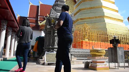 Asian thai people respect pray and travel and posing take photo at gold chedi of Wat Phra That Cho Hae temple in Phrae, Thailand