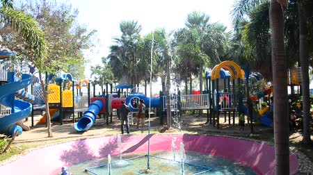 Asian thai children relax playing at modern colorful playground on yard in public garden park of Bueng Boraphet in Nakhon sawan, Thailand
