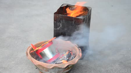 заслуга : People burn joss paper gold and silver paper for worship with paper made to resemble money and burned as sacrificial offering for pray to god and memorial to ancestor in Chinese new year day at house Стоковые видеозаписи