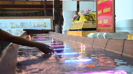 заслуга : Ritual praying colorful candle floating on water for pray buddha at Wat Phra Non Chakkrasi Worawihan in Sing Buri, Thailand. Стоковые видеозаписи