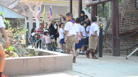 harcerz : Thai student boys and girls scouts walking and pray buddha statue at Wat Pho Kao Ton in Sing Buri, Thailand.