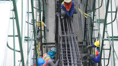 Asian thai worker and heavy machinery working builder new building at a construction site building high-rise building in Nonthaburi, Thailand 影像素材