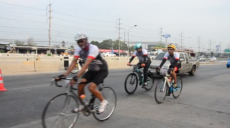 Thai people biking bicycle in race on street highway with traffic road at Bangbuathong city in Nonthaburi, Thailand