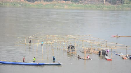binário : Thai worker people demolition wooden structure of floating restaurant in Mekong river because flood at Kaeng Khut Khu in Chiang Khan city in Loei, Thailand