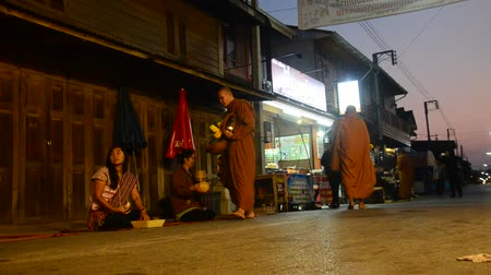 khan : Thai people put food offerings to monks procession walk on the road of tradition of almsgiving with sticky rice at Chiang Khan in Loei, Thailand.