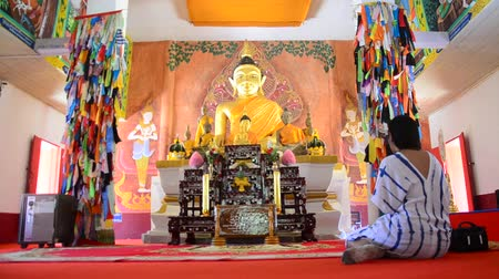 заслуга : Asian thai woman visit and praying buddha statue in ubosot at Wat Phon Chai and travel Phi Ta Khon Museum in Loei, Thailand.