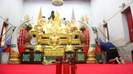 заслуга : Thai people respect praying and gild cover with gold leaf on Luang Pho Ban Laem statue at Wat Phet Samut Worawihan in Samut Songkhram, Thailand Стоковые видеозаписи