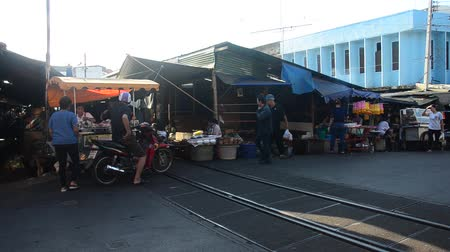romênia : Thai people buy product and food with traffic road and railway with travelers visit at Maeklong Railway Market in Samut Songkhram, Thailand