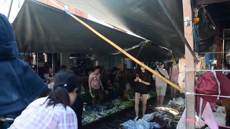 maeklong : Travelers people visit and looking Mae klong Railway Market or Talat Rom Hup meaning the umbrella pulldown market in Samut Songkhram, Thailand