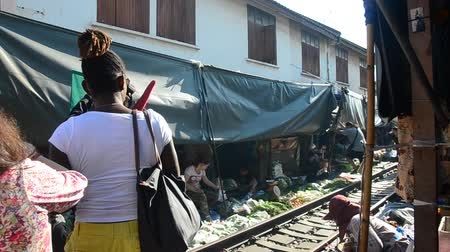 samut : Travelers people visit and looking Mae klong Railway Market or Talat Rom Hup meaning the umbrella pulldown market in Samut Songkhram, Thailand