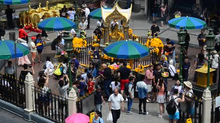заслуга : View of the Hindu shrine from BTS Skytrain and Thai and foriener people praying Thao Maha Phrom or Lord Brahma Great at Erawan Shrine in Bangkok, Thailand