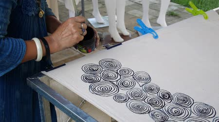 bennszülött : Thai women create and making batik tie dye mauhom  natural color process paint and draw detail and fine line designs on fabric at workshop in Phrae, Thailand Stock mozgókép