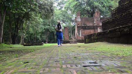 archeological : Travelers thai woman walking and visit ancient building and ruins of Kamphaeng Phet Historical Park is an archeological site and Aranyik Area in Kamphaeng Phet, Thailand Stock Footage