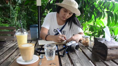 liste : Travelers thai woman drink coffee after writing note on the book for write blog at cafe and restaurant in Tak, Thailand Stok Video