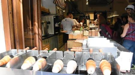 bagietka : People making and grilling bread prague style called Trdelnik for sale and popular in Czechia at.restaurant in Prague, Czech Republic Wideo