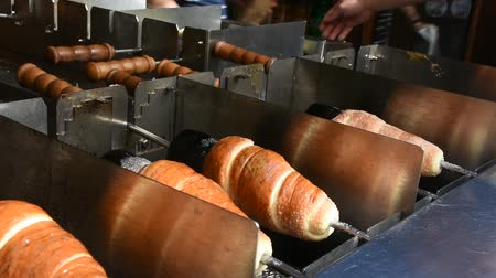 pastelaria : People making and grilling bread prague style called Trdelnik for sale and popular in Czechia at.restaurant in Prague, Czech Republic Stock Footage