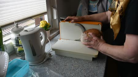slicer : Germany old women use bread slicer or bread cutter cutting bread at kitchen in home in Heidelberg, Germany
