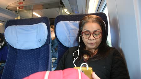 anni sessanta : Asian thai old woman playing mobile phone and listen music while sit on train running from France go to Germany on September 7, 2017 in Nuremberg, Germany