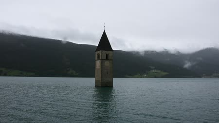 submerso : Submerged tower of reschensee church deep in Resias Lake while raining at morning in Trentino-Alto valley in South Tyr or Alto Adige in Bolzano or bozen city at Italy