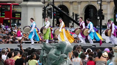культурный : London, UK - August 9, 2015: Korean ethnic dancers perform, Jindo Bukchum, drum dance, in the Korean Festival  at Trafalgar Square, spectators present.