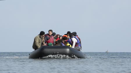 asylum seekers : LESVOS, GREECE March 03, 2016: Refugees arriving in Greece in dinghy boat from Turkey. These Syrian, Afghan and African refugees land Their boat at the coast of Lesvos near Mytilene.