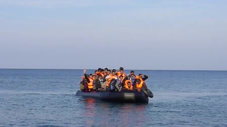 asylum seekers : LESVOS, GREECE October 19, 2015: Refugees arriving in Greece in dinghy boat from Turkey. These Syrian, Afghan and African refugees land Their boat at the North coast of Lesvos near Molyvos.