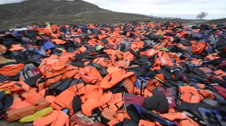 eftalou : Mountain of Life Jackets left by refugees. These Syrian, Afghan and African refugees land Their boat at the coast of Lesvos near Molivos, Eftalou Stock Footage