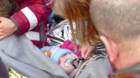 lifesavers : LESVOS, GREECE February 25, 2016: Doctors checking babies and children with hypothermia. These refugees came by dinghy boat crossing the Aegean sea from Turkey to Lesvos.