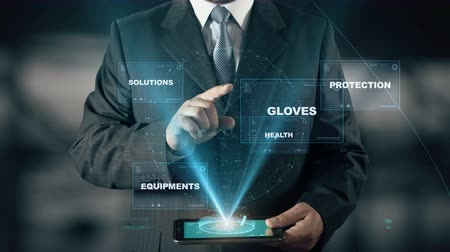 biztonság : Businessman with Work Safety hologram concept choose Gloves from words