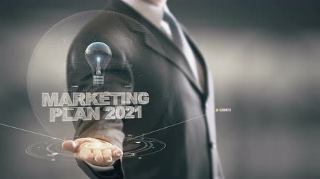 izzók : Marketing Plan 2021 with bulb hologram businessman concept Stock mozgókép