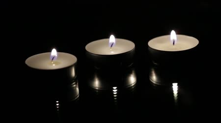 Candle trio against black background Stok Video
