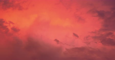 Beautiful dramatic nature clouds in red, orange, purple sunrise. Meteorology cloudscape environment. Dynamic close up shot filmed in 4k UHD