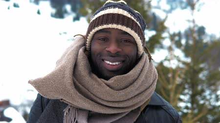 Slow motion. Beautiful trendy black african american man portrait face. Male smiling wearing a hat and a scarf. Static winter close up shot filmed in 4k UHD 2160p