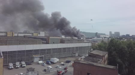 Helicopters extinguish a fire in an industrial building.