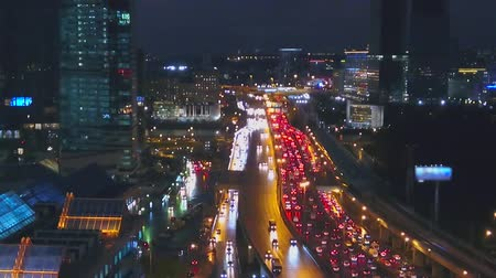 In the frame, you can see the windows of offices in a high-rise building. Then the camera moves to the right. In the picture, a traffic jam in a large city. Dostupné videozáznamy