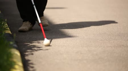 impaired : A blind man gropes his way with a cane. Stock Footage