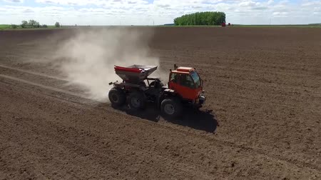 The fertilizer spreader moves across the field of dry fertilizers. The camera flies over the car.