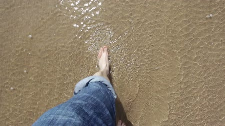 anonymní : Point of view looking down at legs with jeans rolled up and bare feet walking on a sandy beach into the sea