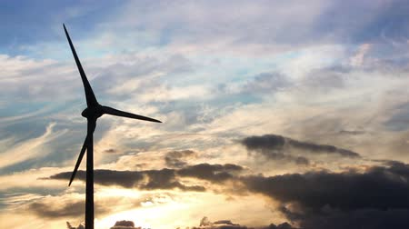 türbin : Rotating wind turbine at sunset, silhouetted against a colourful sky with moving clouds. Copy space to the right of frame.
