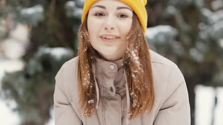 free throw : Young woman blows handful of snow at camera, slow motion