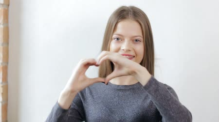 braces smile : Teen girl with braces making love heart gesture with hands Stock Footage