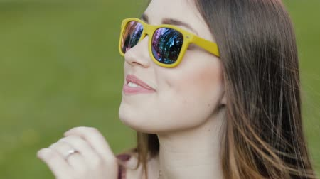 espetáculos : Portrait of young woman sitting on grass in sunglasses Stock Footage