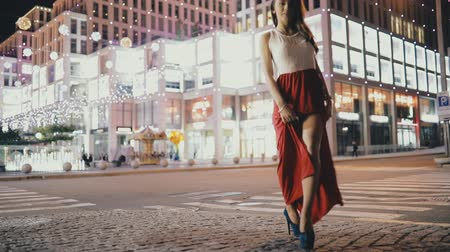 соблазнять : Seductive woman in beautiful red dress with sexy legs walking in night city street