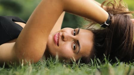 coquettish : Attractive woman lying on grass at summertime, she relax and coquettish play with hair.