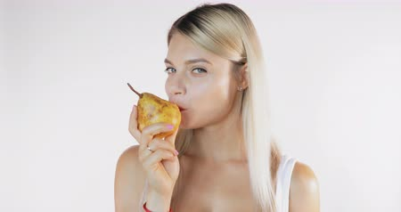 munch : Attractive woman in shirt eating a big juicy pear isolated on white background with sound Stock Footage